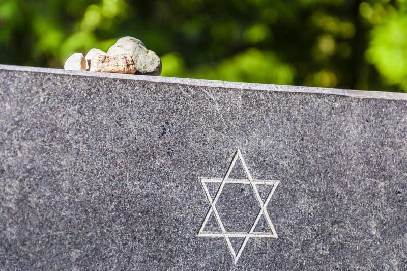 Steine auf jüdischer Erinnerungsgranitplatte mit Davidsstern stockfoto