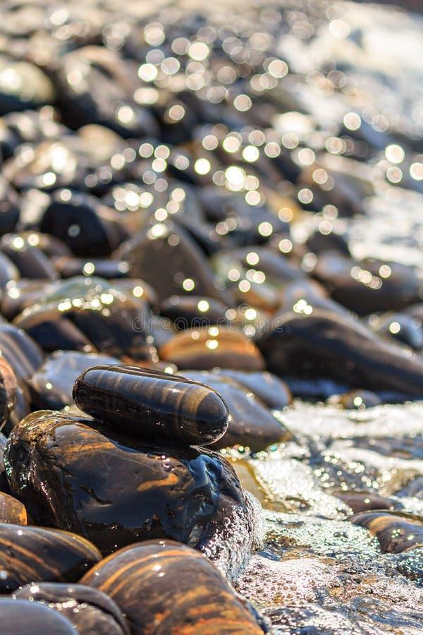 Steine auf Strand- und Seewelle lizenzfreie stockfotos