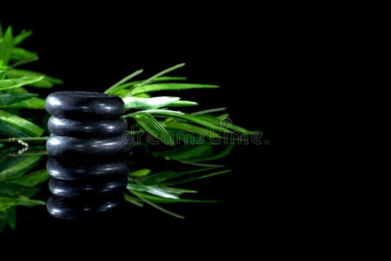 Steine für den heathy Badekurort und Behandlung mit Grün verlässt auf dunklem Hintergrund und Reflexion lizenzfreie stockfotos