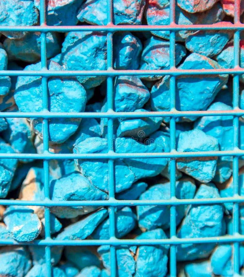 Steine gemalt mit blauer Farbe in einem Metallgitter als Hintergrund lizenzfreie stockbilder