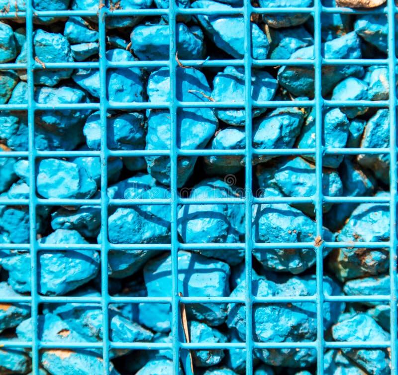 Steine gemalt mit blauer Farbe in einem Metallgitter als Hintergrund stockfoto