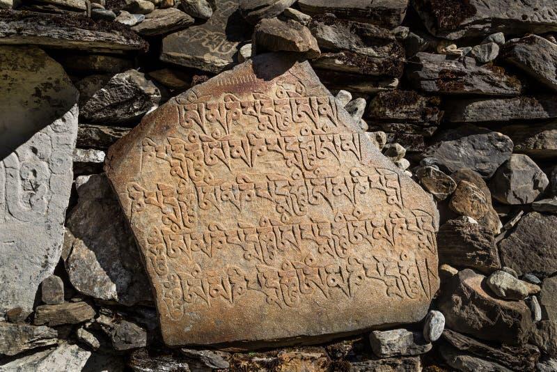 Steine geschnitzt mit nepalesischen Charakteren lizenzfreies stockbild