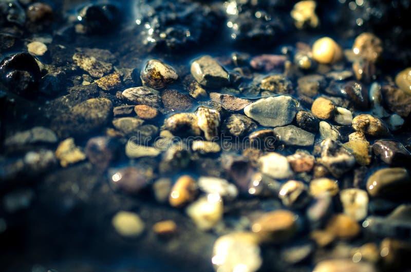 Steine im Flussbett stockbilder