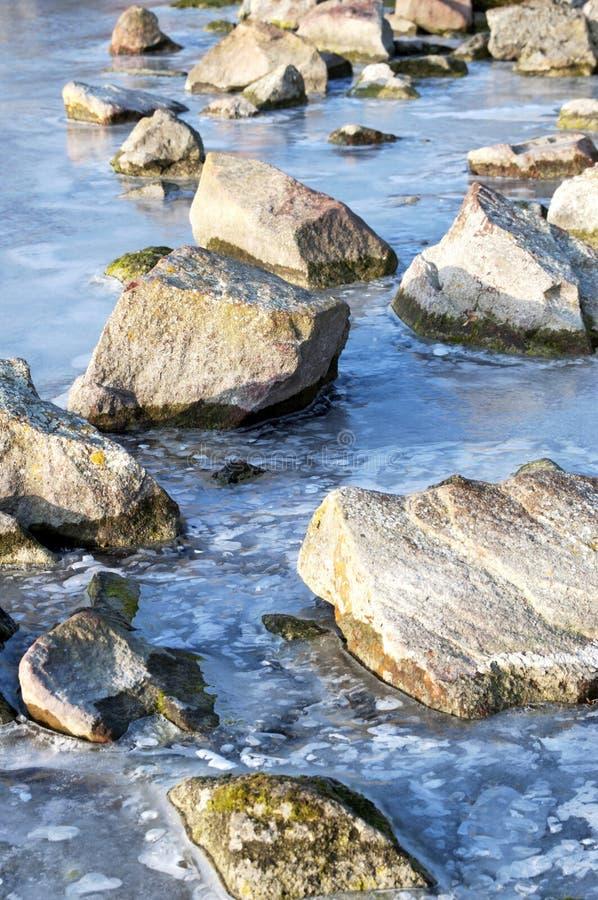 Steine im gefrorenen See stockbild