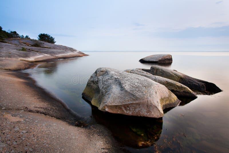 Steine im ruhigen Meer lizenzfreie stockfotos