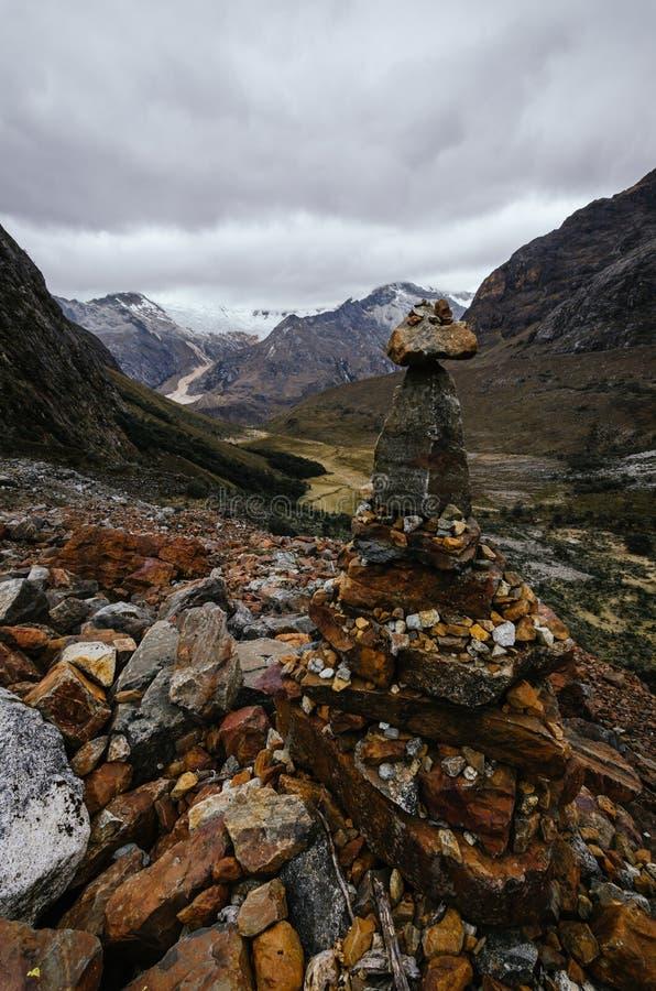 Steine im Vordergrund mit den Überresten einer Lawine im Hintergrund auf dem Trekking der Quebrada santa Cruz stockfoto