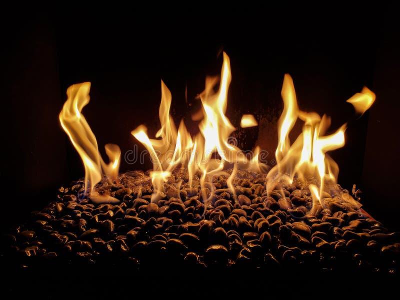 Steine in Kamin mit Flammen stockbilder