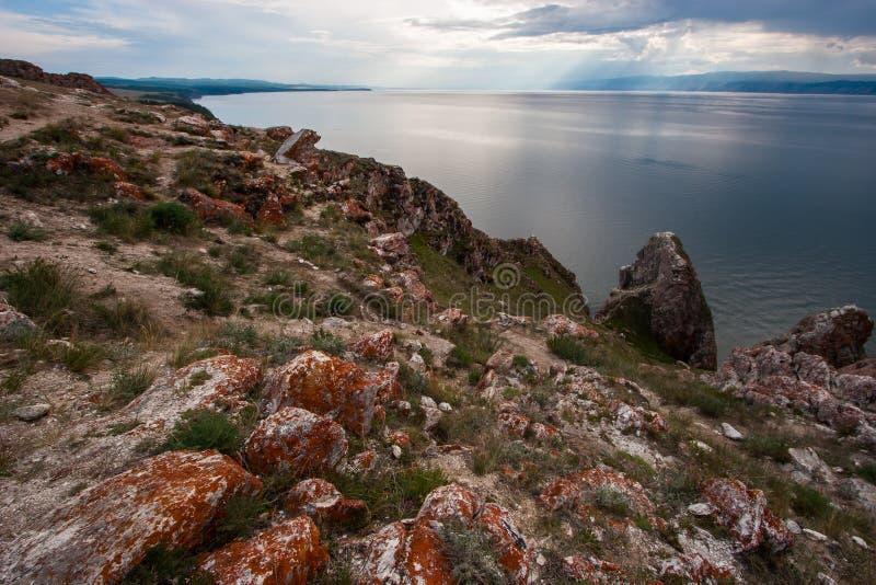 Steine mit rotem Moos auf den Felsen vom Baikalsee auf Olkhon-Insel Zwischen dem grünen Gras der Steine Berge hinter dem See stockfotografie