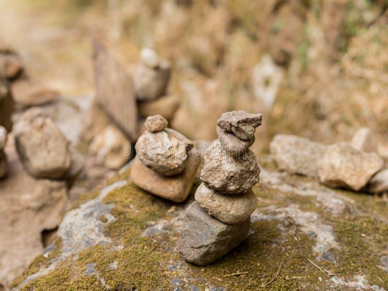 Steine sind auf einem Felsen ausgeglichen, der mit Moos im Park bedeckt wird stockfotografie
