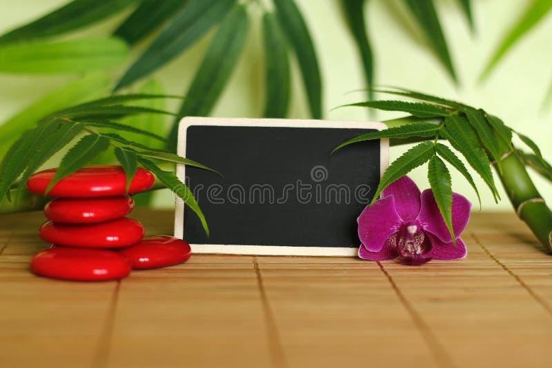 Steine vereinbarten im Zenlebensstil mit einer Orchidee, eine brennende Kerze, eine Bambusniederlassung und ein Laub und ein Sche lizenzfreie stockbilder
