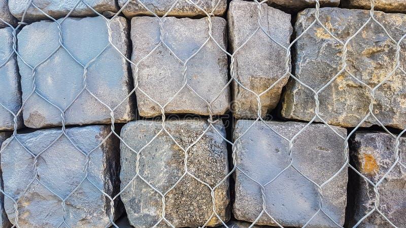 Steinfelsen-Ziegelsteine hinter Metallzaun-Wall Wallpaper Background-Beschaffenheit Schließen Sie oben von den enormen Steinfelse lizenzfreie stockbilder