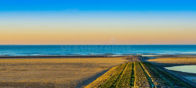 Steingehweg von den Felsen, die zu das Meer, schönen Strand bei Sonnenuntergang in Blankenberge, Belgien führen stockfotos