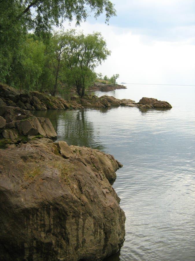 Steinige Bank des Dnieper-Flusses an einem windstillen Sommertag lizenzfreies stockfoto