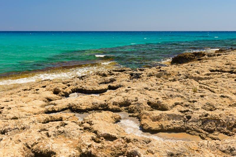 Steinige Küste des azurblauen Meeres stockfoto
