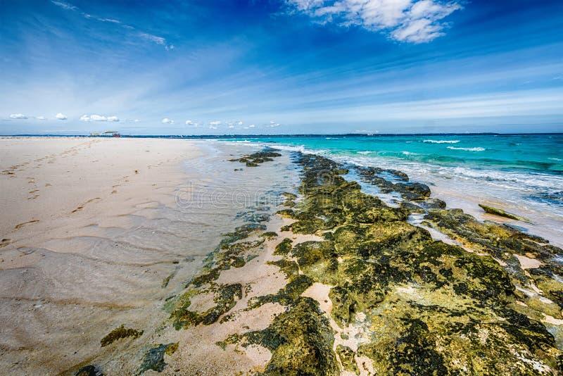 Steinige Küste und klares Wasser mit blauem Himmel auf dem Hintergrund stockbilder