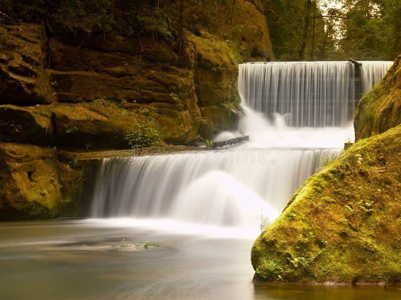 Steiniges Wehr auf kleinem Gebirgsfluss Strom fließt über Blöcke und macht milchiges Wasser stockbilder