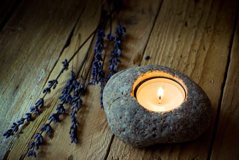 Steinkerzenhalter mit Teelicht auf Scheunenholz, Lavendelzweige, Ostern, Ruhe stockfoto