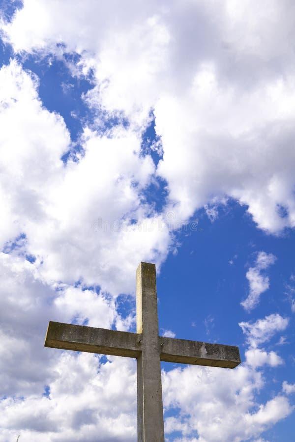 Steinkreuz hinter Wolken gegen blauen Himmel stockfoto