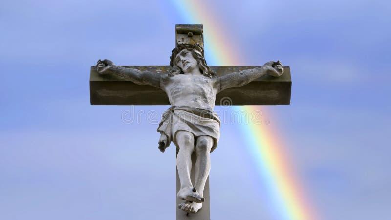 Steinkreuz mit Jesus und blauem Himmel mit Regenbogen stockbilder