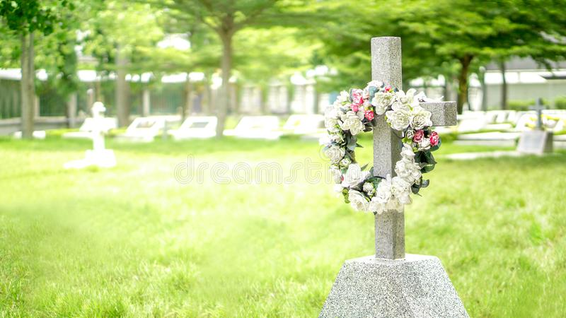 Steinkreuz und Grab im Friedhof mit Flammenzündungseffekt und Leerstelle kopieren stockfotografie