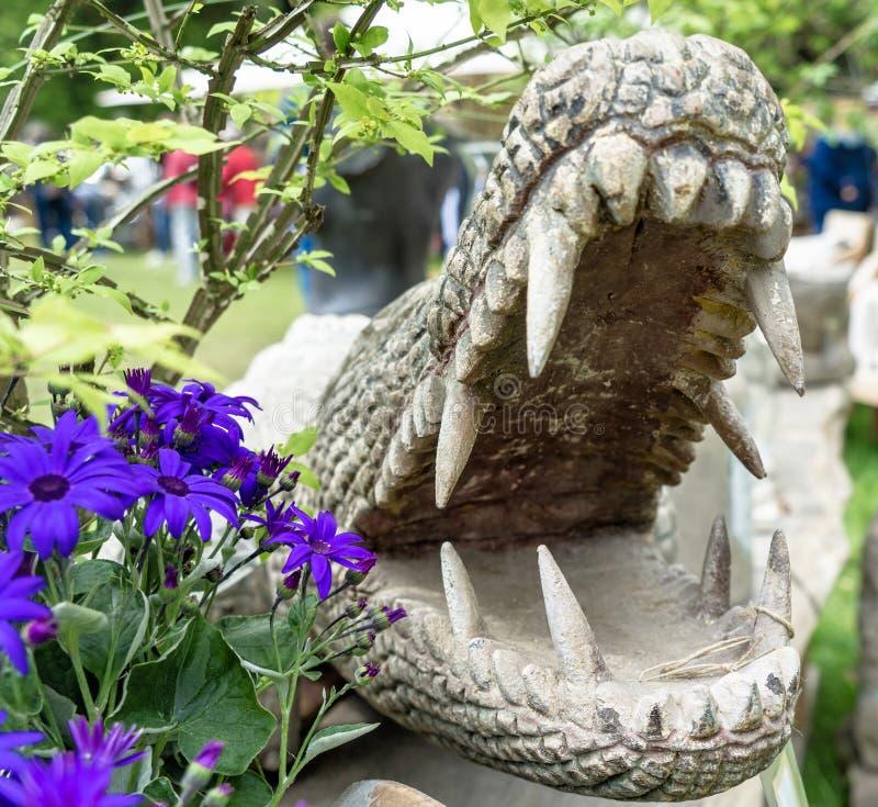 Steinkrokodil mit weit offenem Mund und enorme Zähne nahe bei violetten Blumen stockbild