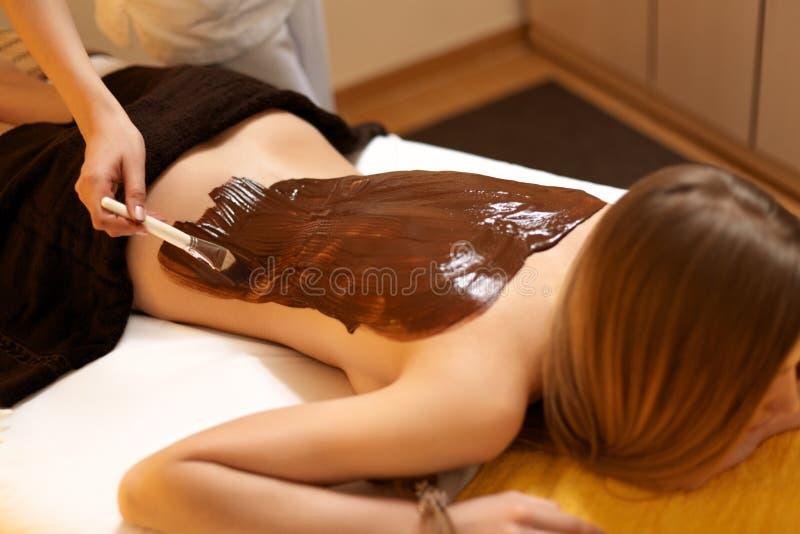 Steinmassage auf Weiß Junge Frau erhält Schokoladen-Körper-Maske am Schönheits-Salon stockbilder