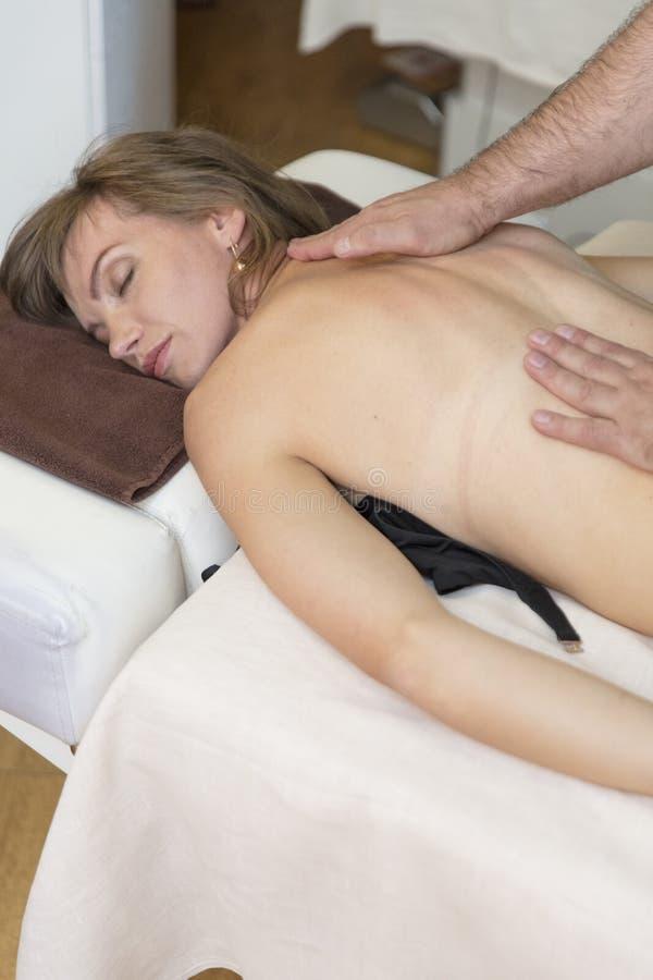 Steinmassage auf Weiß Junges Mädchen, das entspannende Rückenmassage in der Cosmetologybadekurortmitte genießt Körperpflege, Haut stockbild