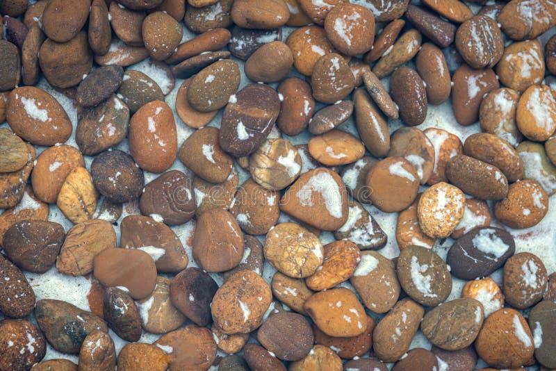 Steinmusterhintergrund die Steine, die im Wasser liegen stockbild