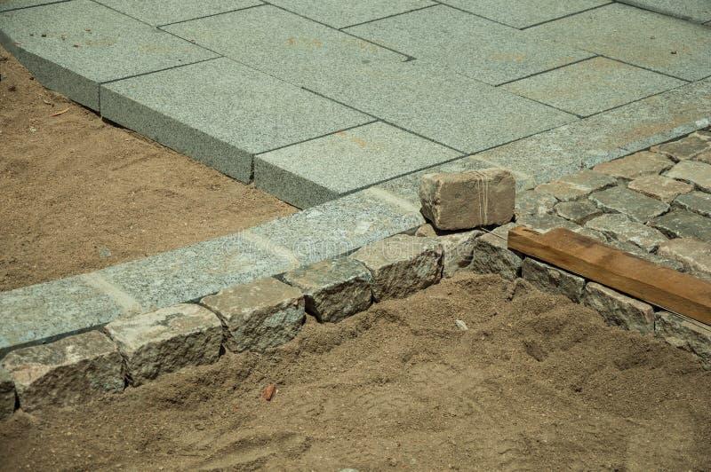 Steinpflastersteinblöcke, die in einer Baustelle Sand-setzen lizenzfreie stockfotografie