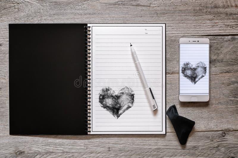 Steinrewritable Papiernotizbuch und Smartphone stockbild