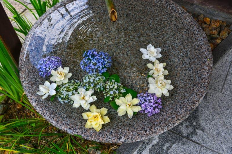 Steinschüssel mit Blumen für Dekoration stockbild