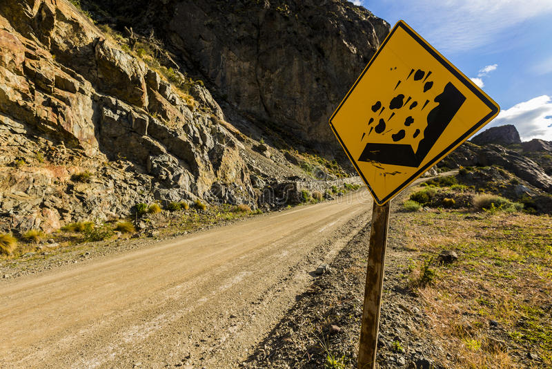 Steinschläge, die Verkehrszeichen auf einer schmutzigen Straße mit Stein- und Himmelhintergrund warnen stockfotos