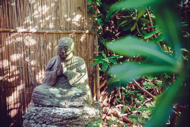Steinstatue des buddhistischen Mönchs Sitting in der Meditation im japanischen Garten Außen-, Dekor im Freien Entspannen Sie sich stockfotografie