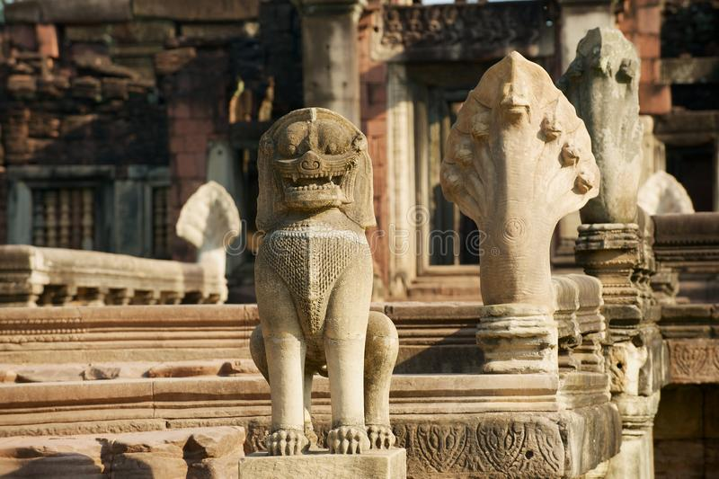 Steinstatuen, welche die Ruinen des hindischen Tempels im historischen Park Phimai in Nakhon Ratchasima, Thailand schützen lizenzfreies stockfoto