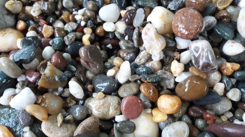 Steinsteinhaufen auf gestreiftem grauem wei?em Hintergrund lizenzfreie stockfotografie