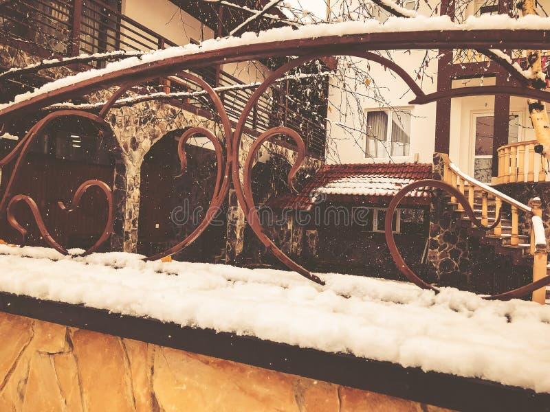 Steintor mit dekorativer Stahlordnung Schneefälle auf der Straße mittag lizenzfreies stockfoto