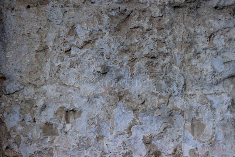 Steinwand mit einer vielschichtigen alten Taumelschwingungstünchebeschaffenheit stockbild