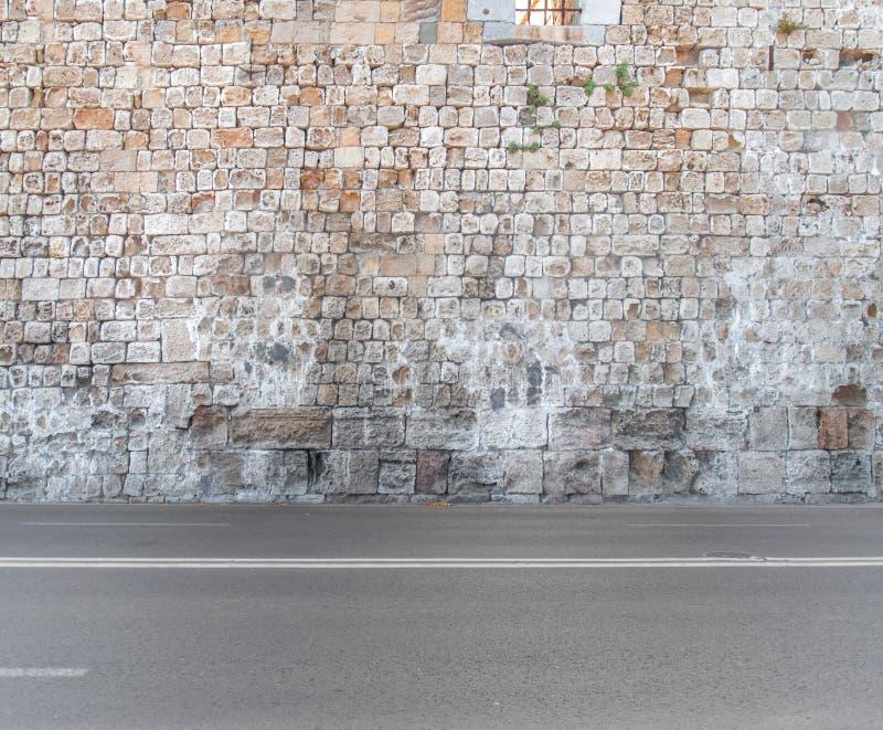 Steinwand- und Asphaltvordergrundbeschaffenheit des großen Schlossblockes lizenzfreies stockbild