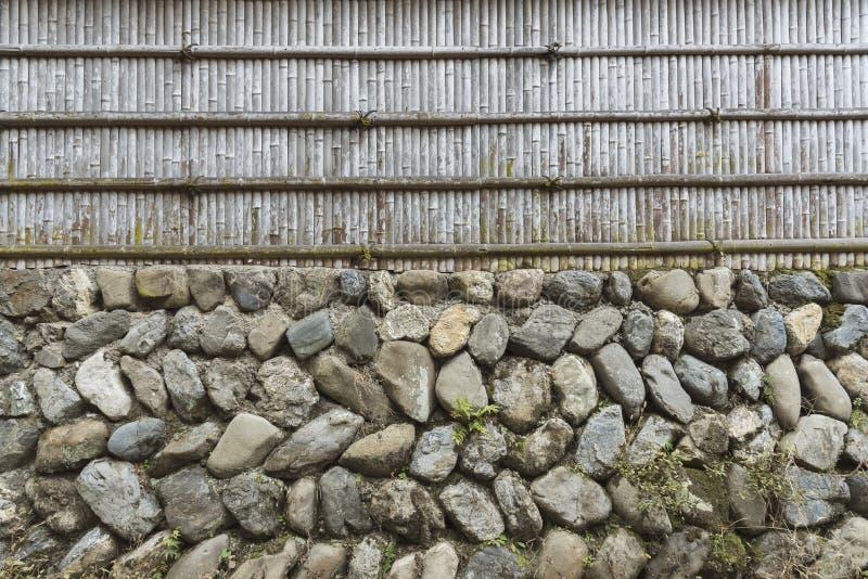 Steinwand- und Bambuszaun lizenzfreie stockfotografie