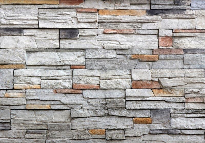 Steinwandumhüllung hergestellt vom grauen Felsen gemischt mit den roten und schwarzen Streifen stockfoto