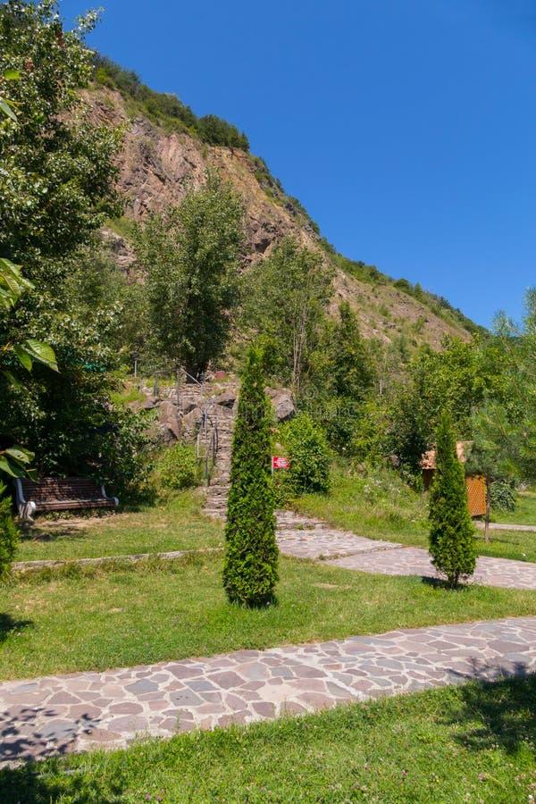 Steinweg im Gras im Park, führend zu Treppe am Fuß des Felsens stockfotos