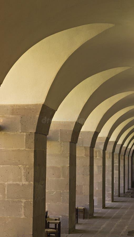 Steinziegelstein-Bogen-Gehweg mit hölzernen Schemeln lizenzfreie stockfotografie