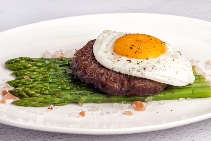 Stek från finhackat nötkött med stekte ägg och ny grön sparris arkivbild
