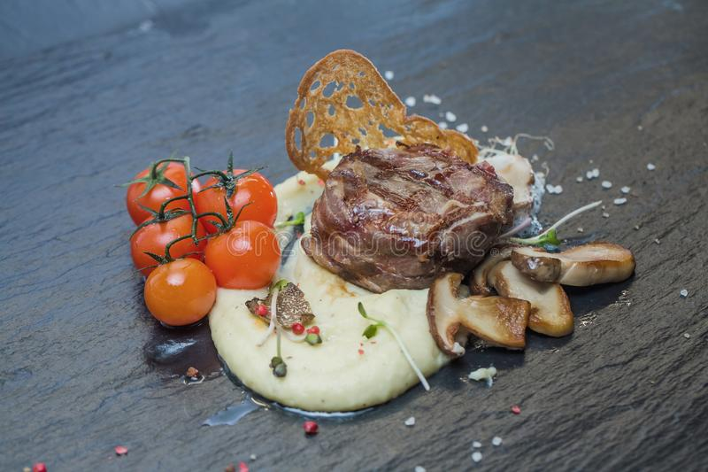 Stek z puree ziemniaczane, dekorującymi z gałąź czereśniowi pomidory, croutons, plasterki ciemny pstrąg i biel, obrazy stock