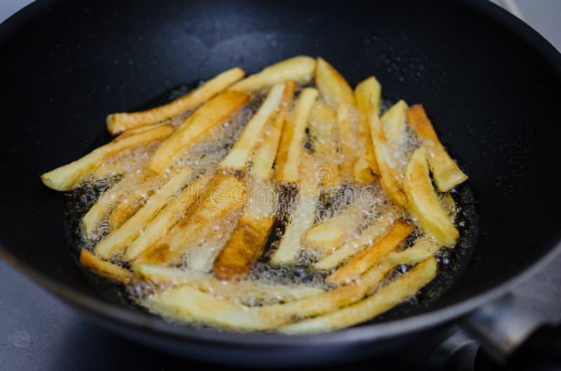 Steka potatisar i en panna royaltyfri foto