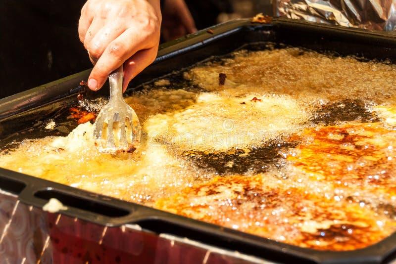 Steka raggmunkar i varm olja Raggmunkar i en panna traditionellt mål greasy mat Faror av fetma fotografering för bildbyråer