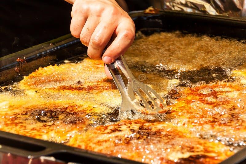 Steka raggmunkar i varm olja Raggmunkar i en panna traditionellt mål greasy mat Faror av fetma arkivfoton