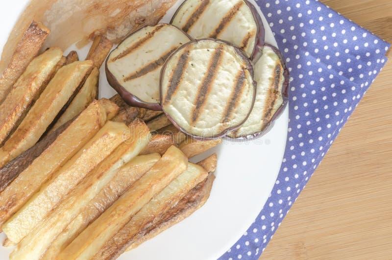 Steker potatisar med grillad aubergine royaltyfri bild