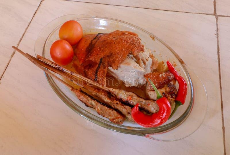 Stekgriskött i ett exponeringsglas som grillar pannan Köttfärs på en träpinne Frasig och guld--bakad hud Peppar för varm chili oc royaltyfri fotografi