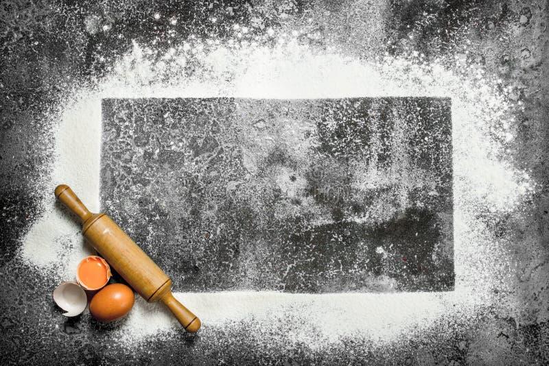 Stekhet bakgrund En ram av mjöl med en kavel och nya ägg royaltyfria foton